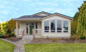 An exterior view of a quality modular home made by DeTray's LLC. Yellow paint and big bay windows, with a stone path leading to a covered small covered entry patio.